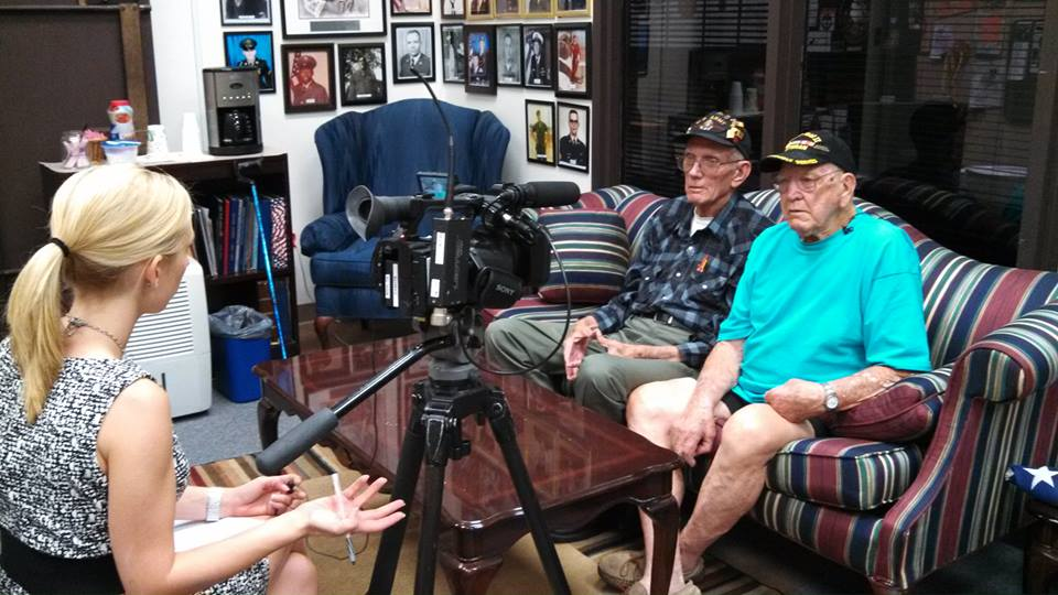 Two veterans sit on a sofa together, being interviewed by reported with a video camera